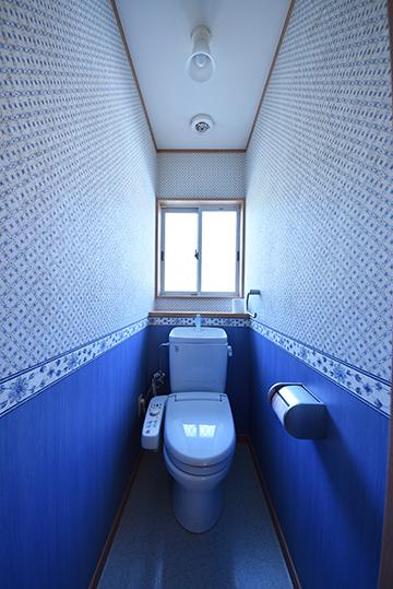 深海ブルーのアクセントクロスが映えるトイレ